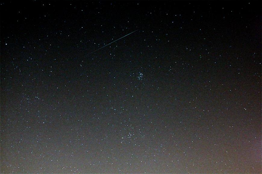 Caldwell 41, die Hyaden (unterhalb der Mitte), sowie die benachbarten Pleiaden und eine Geminiden-Meteor.